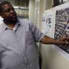 Milton Bolton, the president of the tenants association at Prospect Plaza, points to plans for what will take the place of the high-rise housing project in Brownsville. It was emptied in 2002 for what was supposed to be a renovation and now will be a demolition.