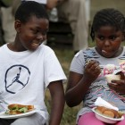 Thomas Sayee, 10, laughs while Nashia Rainey, 8, tries pudding she had never had before during lunch.
