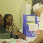 Inspectors Laronda V. Lockert and Diane Stafford assist voter Agustin Gonzalez at the Glebe Avenue Senior Center polling station.