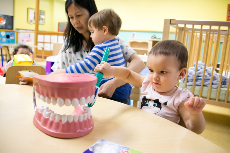 16-month-old Livia practices brushing teeth while 21-month-old Gunnar sits in Infant Care Aid Jian Liang's lap reading a book at the Magical Years Early Childhood Center, part of the Lutheran Family Health Centers.
