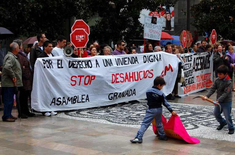 A protest against foreclosures in Spain shares space with a party for a local bullfighting school.