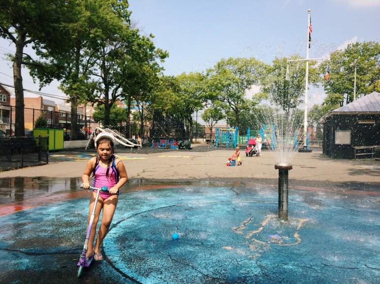 Scooting and splashing through the cooling spray at Loreto Playground.