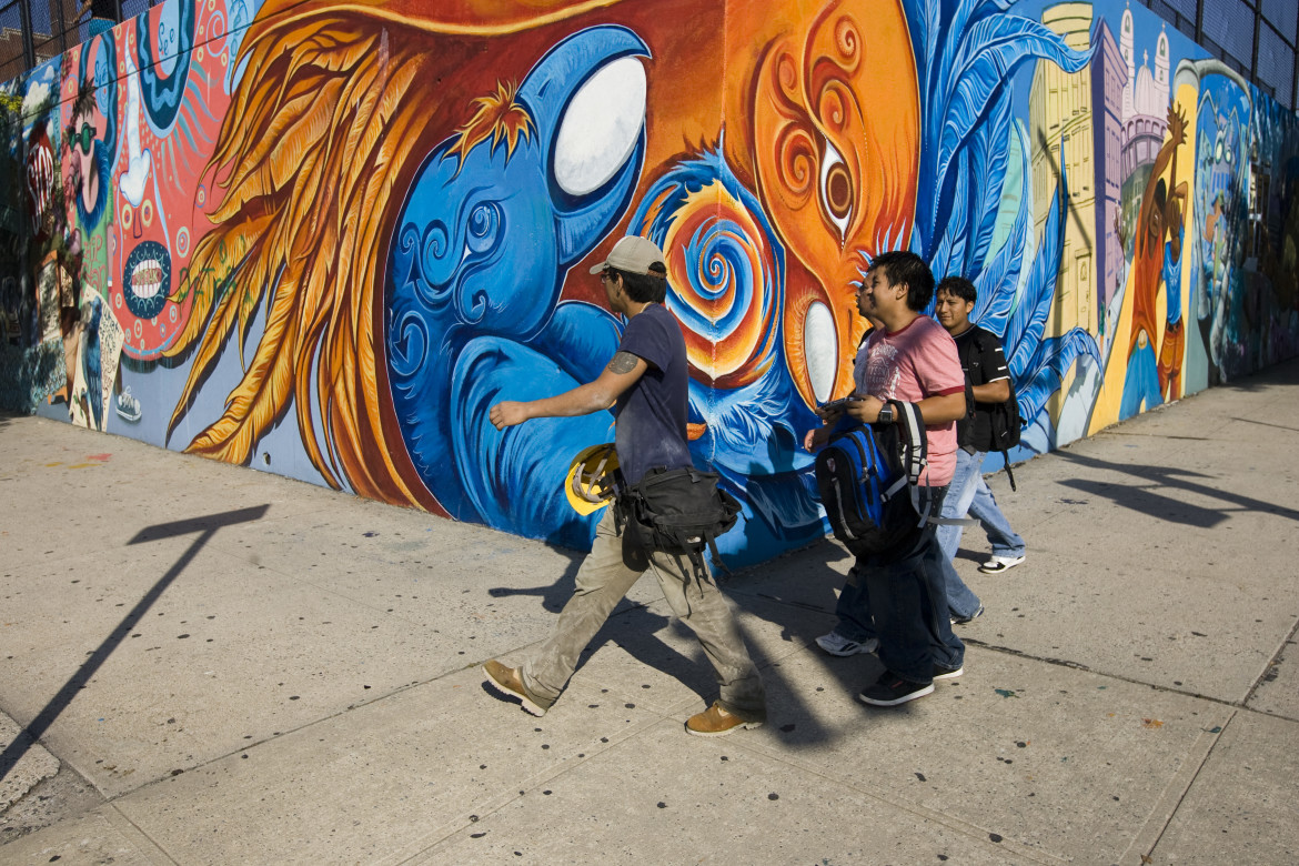 People walk passed a mural near a high school in Bushwick, New York. Photo by J. Silberberg contact: jacobsilberberg@yahoo.com 617-413-8659