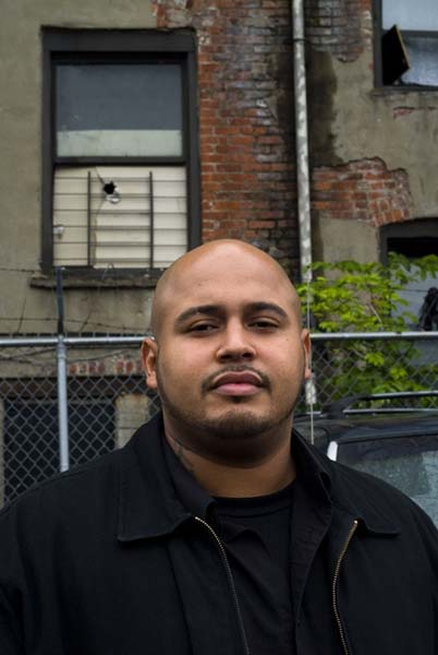 Cesar Guzman, 28, outside of the building where his family lives at 422 East 178th Street in the Bronx. The exterior is deteriorating, as well as the interior. Guzman blocked off the window, which was missing a pane.
