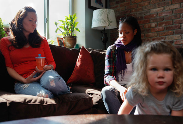 Sara Monestime (in red) of 201 Spencer Street and Kwana Lamar-Reinoso of 195 Spencer Street in Brooklyn discuss the problems with their buildings, as two-year-old Madelyn Monestime looks on.