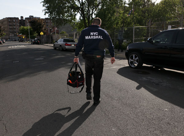 City Marshall Oren Varnai walks back to his car after helping a Con Edison worker seize a gas meter from a delinquent customer in the Bronx. Varnai's application process to become a marshal took three years until he was appointed by the mayor.