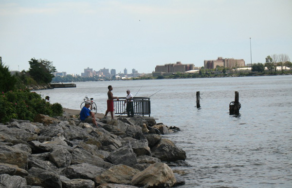 Fishermen at Barretto Point Park in the Bronx, with the buildings of Rikers Island in the distance. A sewage plant, floating correctional facility and half-dozen waste transfer stations are nearby, and the area hosts heavy truck traffic.