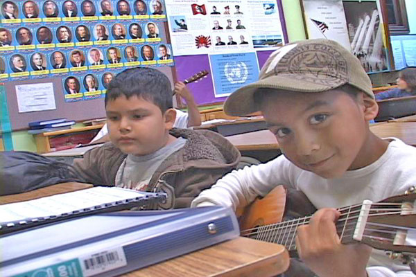 Children at the Mariachi Academy of New York in East Harlem learn to play guitar during a mariachi class.