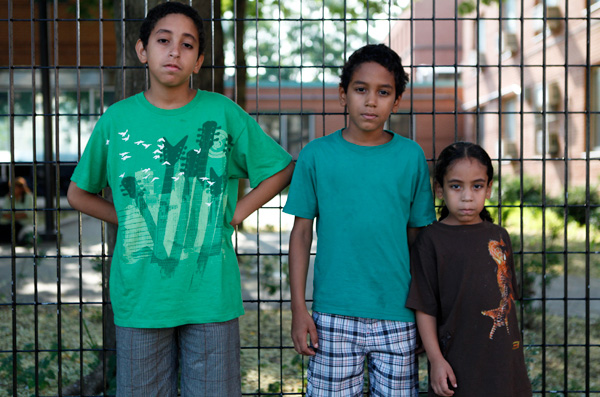 Brothers Erickson Morales, 10, Erick Morales, 9, and Roeriel Morales, 5, pose outside the PATH Center in the Bronx, where they are currently living. They are enrolled in PS 399 in Brooklyn in the fall, but they do not know where they will be living when school starts.