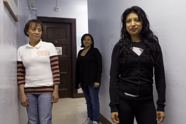 Members of Si Se Puede, a cleaning cooperative, stand behind Yadira Fragoso after a meeting in Sunset Park, Brookly