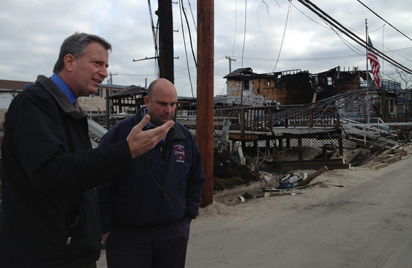 Public Advocate Bill de Blasio touring storm-damaged Breezy Point in November. After the Newtown shooting, de Blasio called for the city's pension funds to divest from gun companies. The NRA, meanwhile, says post-Sandy looting is an argument for all responsible citizens to arm themselves.