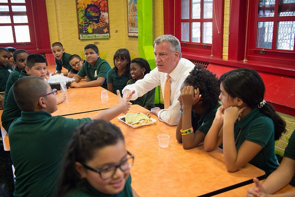 Mayor Bill de Blasio has lunch with students at P.S. 69 in the Bronx during the first-day-of-school five-borough tour. His UPK program, which debuted that day, and affordable housing plan are aimed at reducing the income gap in the city.