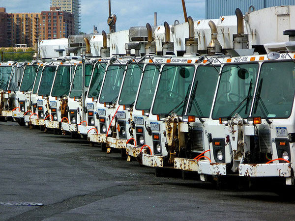 Department of Sanitation garbage trucks sit idle in a parking lot. Because the city doesn't haul commercial waste, it has had little information about how much businesses are actually recycling.
