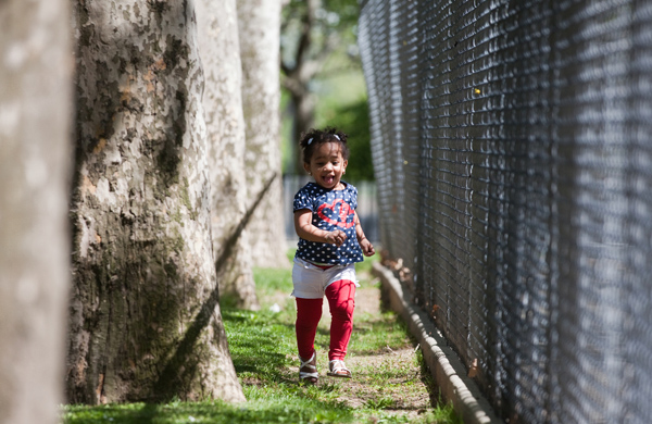 Madeline Alcanatara, 2 years old, runs along the fence of a playground in the Wagner Houses in census tract 192, one of the poorest in the city.