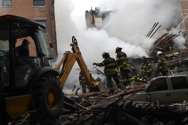 Firefighters search through the rubble of two buildings in Harlem that exploded Wednesday morning. The death toll was expected to rise.