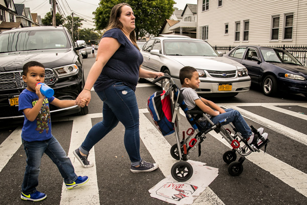 Lorraine Doucette crossing the street with her sons Liam (4 years old, walking) and Jason (6 years old, in the chair) on their way to pick up her daughters from school, a few block away from their home. Lorraine struggled to get Jason's public school to provide the services he needs.