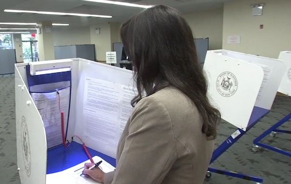 In a scene from a Board of Elections instructional video, a voter uses the