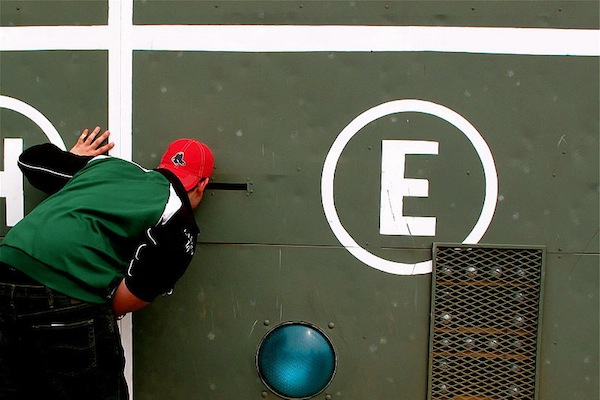 A fan checks out the scoreboard at Fenway Park – site of the World Series game that will follow on the heels of tonight's debate featuring Bill de Blasio's Red Sox. The candidates will almost certainly make grinning reference to the game, though the joke will lose its edge faster than a hanging curveball if tried too often.