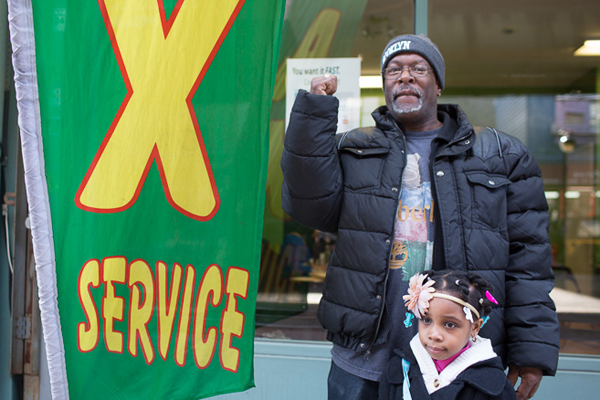 Danny Taylor poses with his daughter outside a tax preparation business